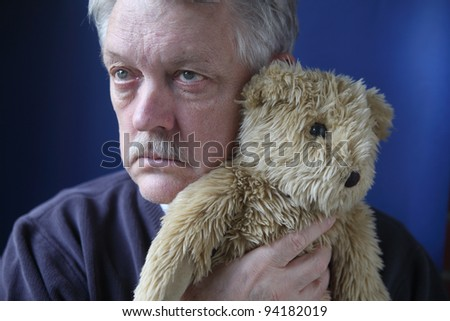 an older man holds a generic stuffed animal close to his face