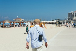 An older man in a flat cap, blue shirt and white trousers walking on a beach in Tel Aviv, Israel