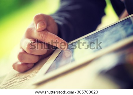 An older man is browsing the internet with a white tablet outdoor. Image has a vintage effect applied.