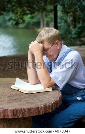 An older man praying by the lake.