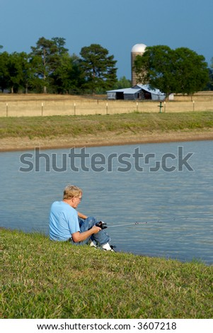 An older man sitting by the pond fishing with a pasture and old barn in the background. - stock photo