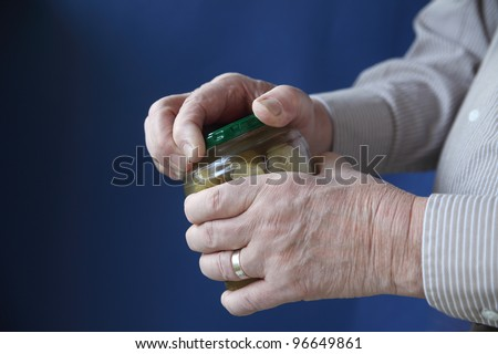 an older man struggles to open a jar of pickles - stock photo
