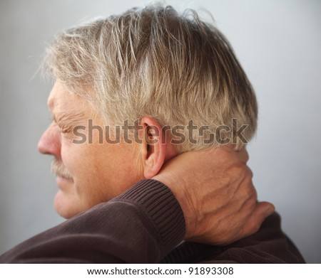 an older man wincing from pain in the back of his neck