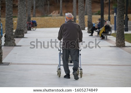 An older man with a walking frame walks on a palm avenue at the Costa Brava in Spain.
