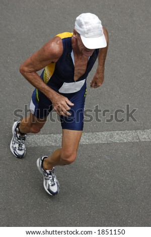 An older runner in a triathlon race, taken from above. Motion blur on his feet.