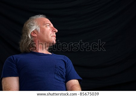 An older white male is looking towards copy space in blue t shirt against black background taken from low angle.