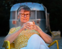 An older woman with glasses holding a cup of coffee is sitting in a yellow chair with her face in the last sunlight in front of an airstream Travel Trailer