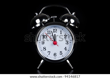 an oldfashioned alarm clock isolates before black background