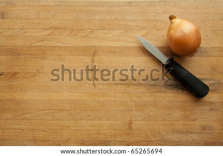 An onion and a knife sit on a worn butcher block cutting board with sufficient room for text