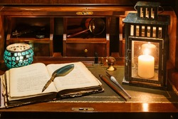 An open antique book in which a magnifying glass and a writing pen rest. are found on a wooden desk on leather. Two lighted lanterns are incorporated to illuminate with a candle