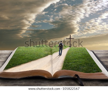 An open bible with grass and a man walking towards a cross - stock photo