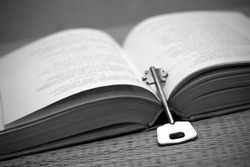 An open book and a key in black and white. Education/wisdom concept with a book and a key.