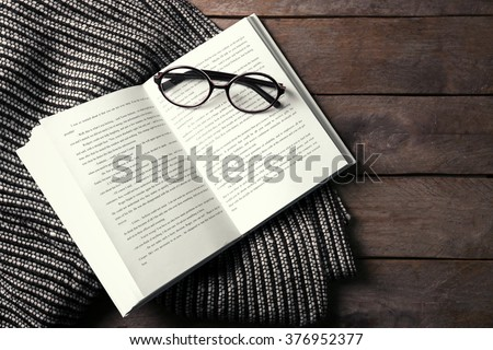 Shutterstock An open book, glasses and a blanket on the wooden background