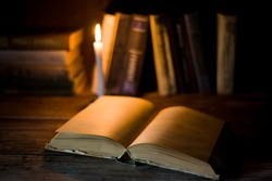 An open book with blank pages lies on a wooden table on the background of other standing books and burning candle.