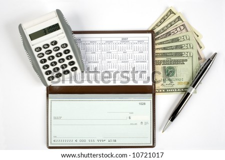 An open checkbook showing the calendar with a pen to the right side. Has a calculator and cash with it.