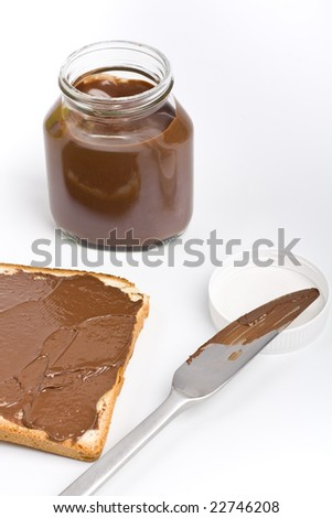 an open chocolate spread container with a buttered toast and a knife