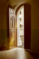An open door from the Church to the outside, sun glare, color illumination, selective focus Concept: you can always come to God, Church rites and holidays.