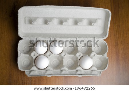An open egg carton with only four eggs in it.