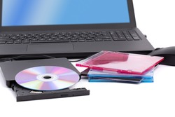 an open external computer DVD CD drive with a pile of CD cases and a notebook computer in the background