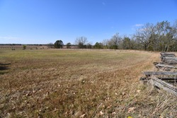 An open field at the Pea Ridge National Battlefield in Garfield, Arkansas. There is a wooden fence. The area was used in a pivotal Civil War battle.