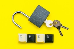 an open lock with keys on a yellow background the word open concept is laid out at the bottom of a computer keyboard. High quality photo