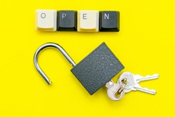 an open lock with keys on a yellow background the word open concept is laid out on top of a computer keyboard. High quality photo