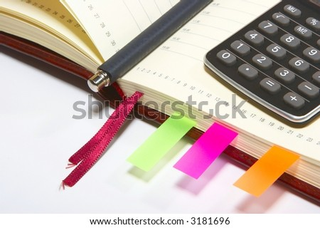An open  notebook with pen and calculator - stock photo