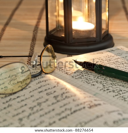 An open old book by the candlelight,close up photo - stock photo