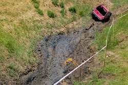 An open pit with slopes and off-road terrain for competition driving through the swamp on off-road vehicles with increased cross-country ability, dirty red car on mud landscape.