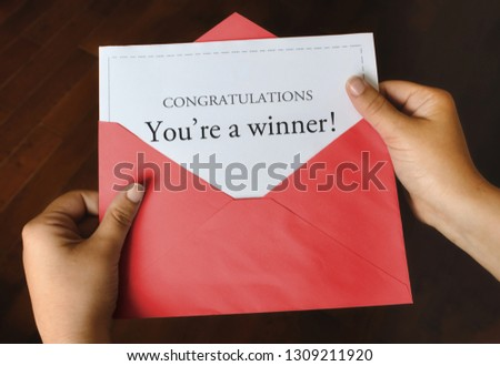 An open red envelope with a letter that says Congratulations You're a winner! with female hands holding it up #1309211920
