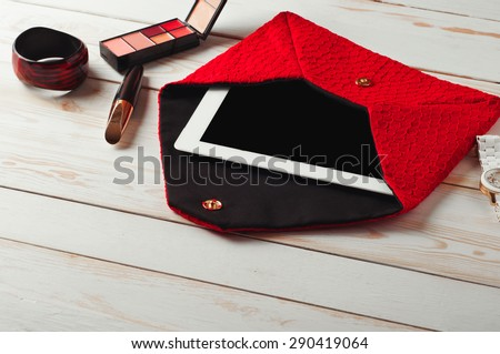 An open red lady\'s bag with tablet computer in a white wooden table.\ Near the handbags are women\'s accessories. Mascara, eye shadow, watch and bracelet
