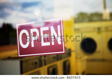 An open sign hanging in a window of a laundromat