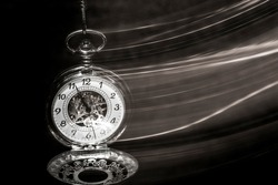 An open silver pocket watch is swinging on its chain, behind it a trail of motion blur. Black background, monochrome picture. The watch symbolises the fleeting of time.