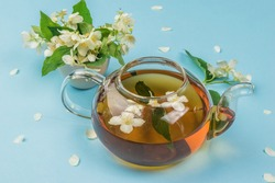 An open teapot with floral tea on a blue background. An invigorating drink that is good for your health.