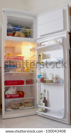 An open white refrigerator with stuff within - stock photo