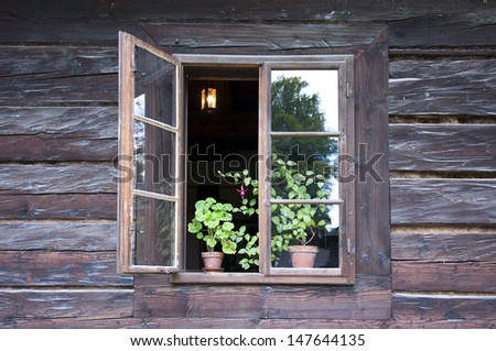 An open window of a old wooden cottage with pot plants on a window sill and and lamp inside, Roznov pod Radhostem, Czech Republic.