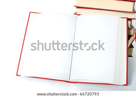 An opened book lies next to a pile of books. Pages with white space for text or else.