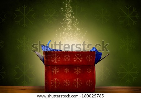 An opened red Christmas gift box with snowflake patterns on wooden table, emitting a magical warm bright glowing light and rising sparkling stars.  Green patterned fabric wallpaper effect background.