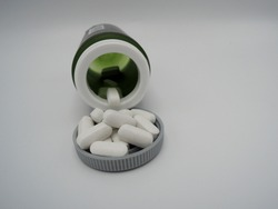 An opened tablet bottle with white tablets of methylsulfonylmethane MSM