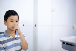 An ophthalmologist used a brock string to maintain vision of an Asian boy's eyes. Eye vision therapy. Select focus.