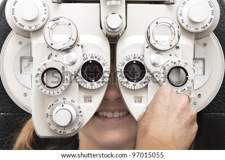 an optometrist adjusts the dials on the phoropter during an eye test
