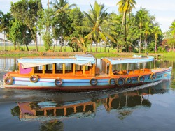 An orange and blue ferry boat on the riverbank of the backwaters in Alappuzha, which is also known as Alleppey, in Kerala, India.