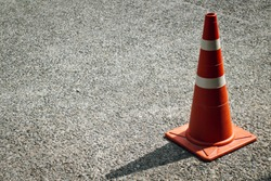 An orange and white stripes traffic cone with shadow from the sunlight on the concrete surface of the parking lot. Copy space.