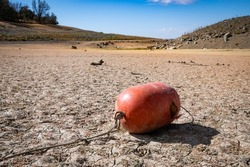 An orange buoy lying on an empty marina area of Folsom Lake California. Water levels are at historic lows due to lack of rain, hot weather and water releases.
