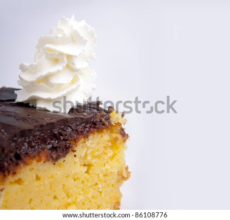 An orange cake with chocolate icing and whipped cream