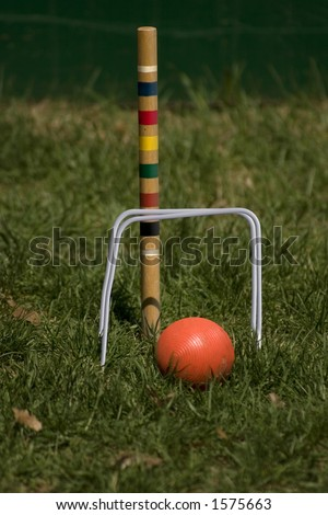 an orange croquet ball heading for the wickets