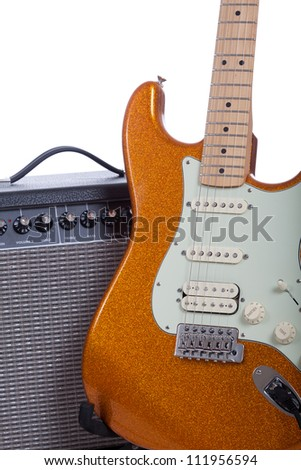 An orange electric guitar and amplifier - stock photo