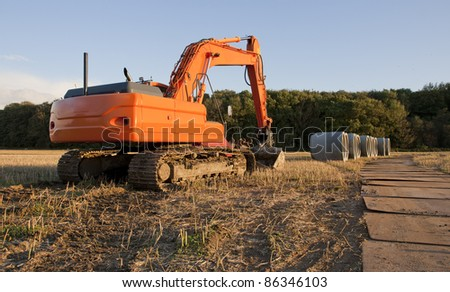 An orange excavator on a field with huge sewer pipes in the background