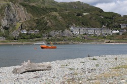 An orange fishing boat moored in the Mawddach Estuary with part of Barmouth, Gwynedd, Wales in the background.