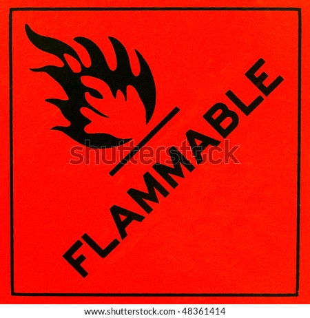 An orange flammable warning sign with black writing